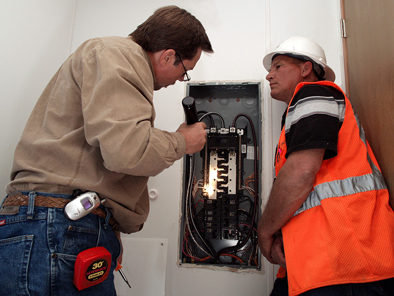 Delzura, CA., December 6, 2007-- Don Keller, right, of Babcock Services, Inc., watches San Diego County Supervising Building Inspector Rusty Anderson, inspect the fuse box inside a FEMA-provided mobile home. He is examining the installation of the home to ensure it is in compliance with local ordinances. The Grice family will temporarily occupy the home while the begin rebuilding their lives following the devastating loss of their home during the October wildfires. Amanda Bicknell/FEMA